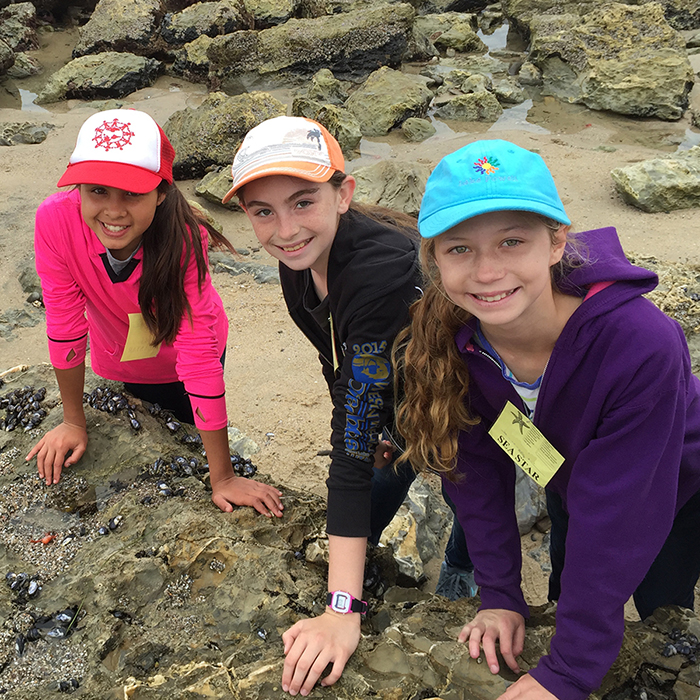 three girls leaning on rock in tidepools