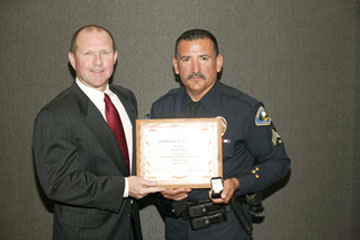 Board Vice President Dr. Kenneth L. Williams with Officer Amador Nunez, Anaheim Police Activities, Junior Cadets Program